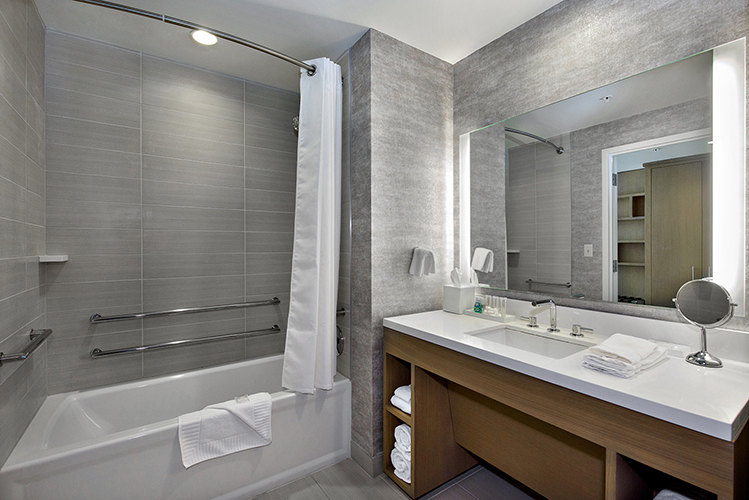 Bathroom with grey walls, white bathtub with shower, and white sink countertop with wood base