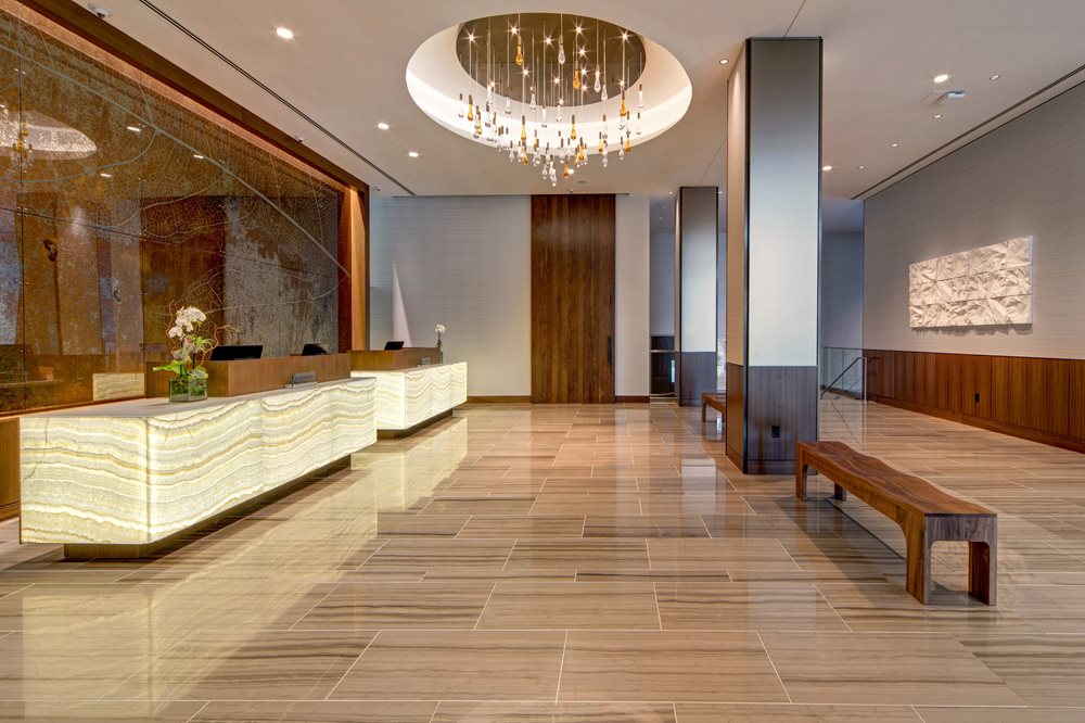 Reception area with two bright desks, tiled floors, and wood grain benches with chandelier above
