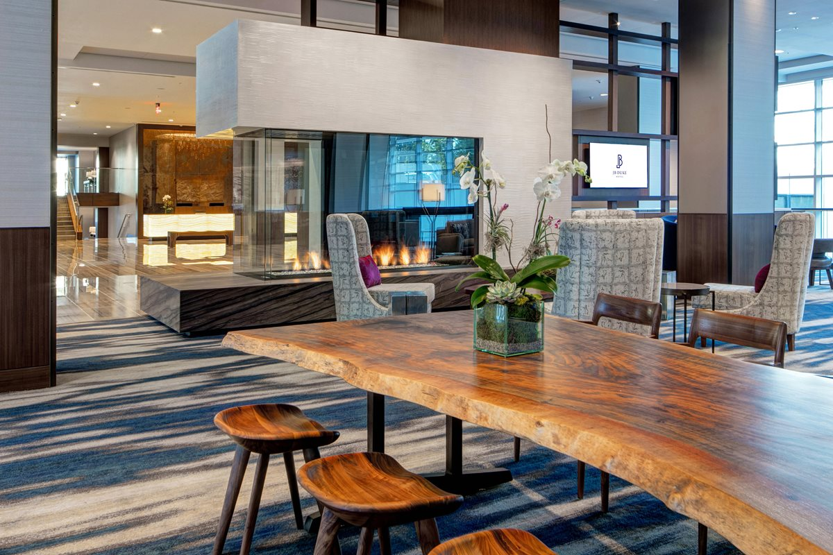 Hotel lobby with a wood grain table and stools, patterned chairs, and a fireplace