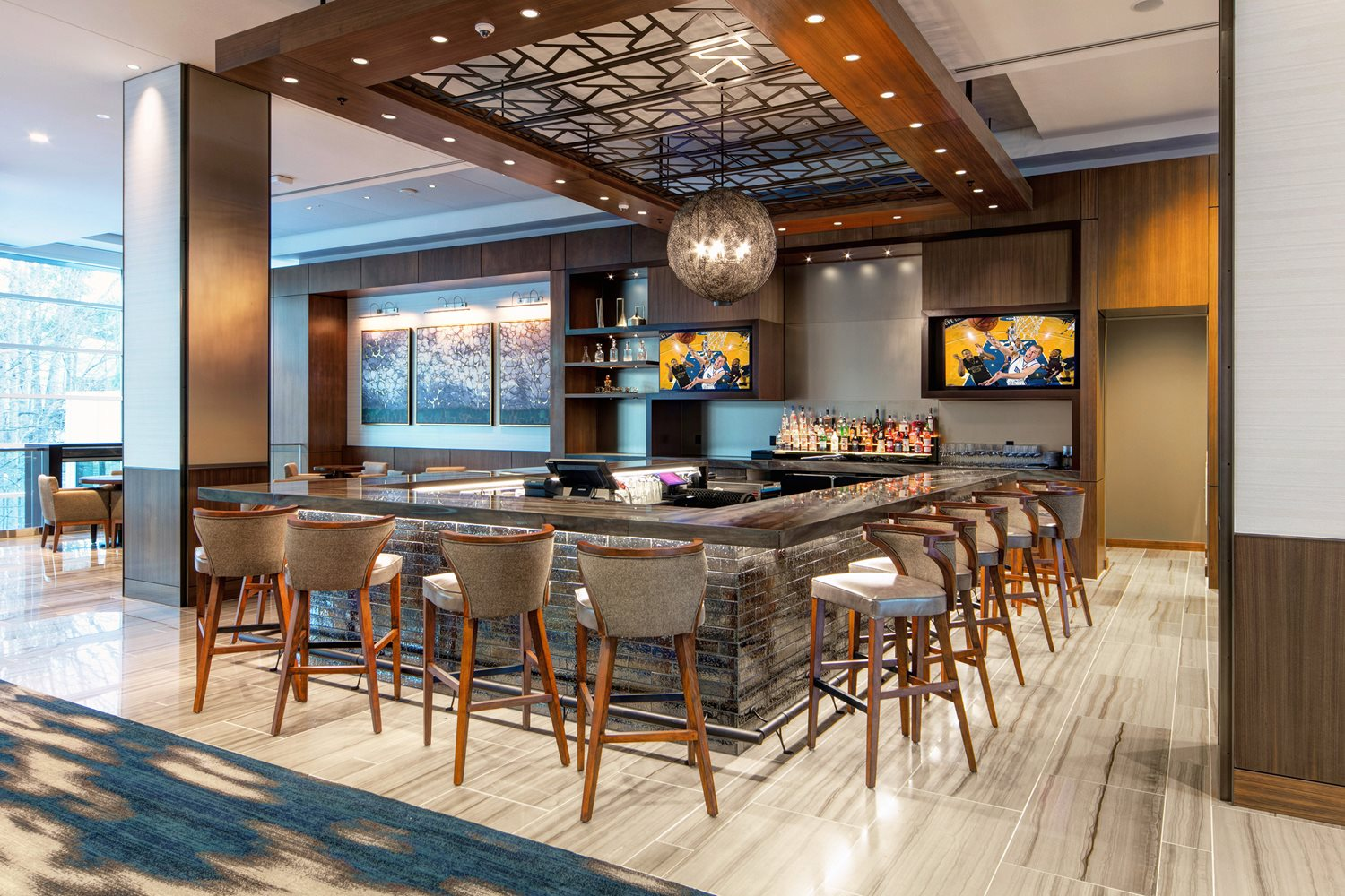 Small bar area with marble countertops, grey stools, and two TVs with fully stocked bar